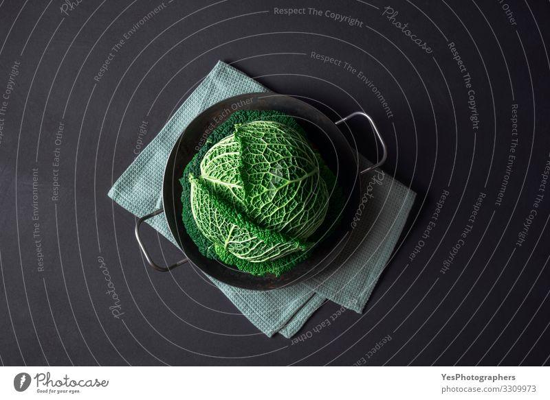 Wirsing in einer Eisenpfanne auf schwarzem Tisch. Kraut kochen Lebensmittel Gemüse Bioprodukte Vegetarische Ernährung Diät Gesunde Ernährung Küche Pflanze