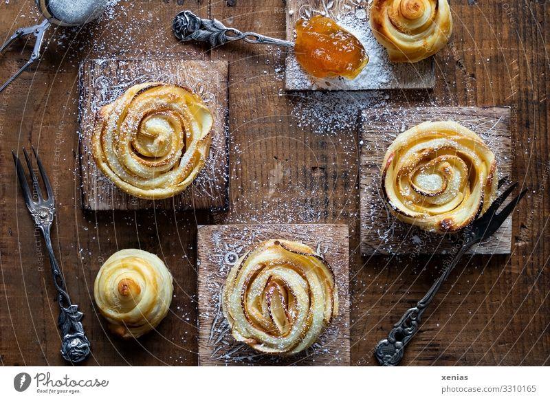 Drei Apfelrosen mit Puderzucker und Aprikosenmarmelade auf Holzbrettchen Lebensmittel Teigwaren Backwaren Kuchen Marmelade Aprikosenkonfitüre Ernährung