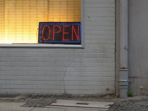 OPEN Stadt rot Haus Fenster gelb Wand Mauer grau leuchten Schriftzeichen dreckig Kommunizieren trist Schilder & Markierungen Hinweisschild Bürgersteig