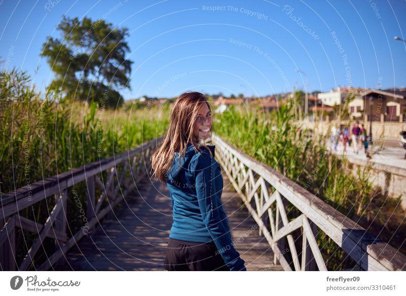Junge Frau geht an einem Holzsteg entlang Lifestyle Erholung wandern Ferien & Urlaub & Reisen Tourismus Abenteuer Freiheit Sommer Jugendliche Erwachsene 1