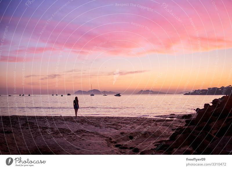 Junge Frau, die über den Sonnenaufgang von einem Strand nachdenkt. Freude Wellness harmonisch Wohlgefühl Erholung ruhig Meditation Freizeit & Hobby
