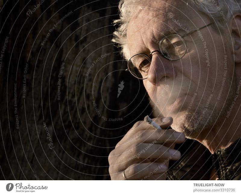 Weißhaariger, rauchender Mann mit Brille und kritischem Blick, brennender Zigarette in der Hand, Ring am kleinen Finger, von der Abendsonne beleuchtet vor dunklem Hintergrund in angeschnittenem Halbprofil untersichtig fotografiert
