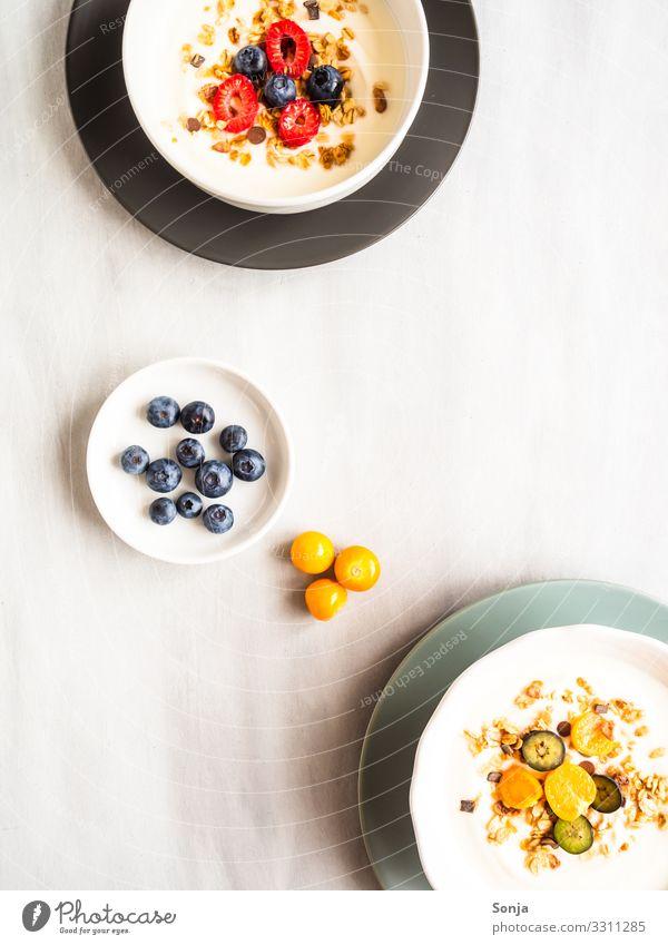 Gesundes Frühstück mit Joghurt, Müsli und Obst Lebensmittel Frucht Himbeeren Blaubeeren Physalis Ernährung Bioprodukte Vegetarische Ernährung Diät Geschirr