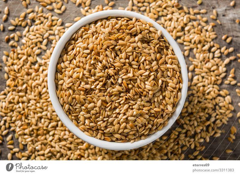 Goldene Leinsamen in weißer Schale auf Holztisch. gold Samen Saatgut Lebensmittel Gesunde Ernährung Speise Foodfotografie Gesundheit Diät Zutaten Getreide Korn