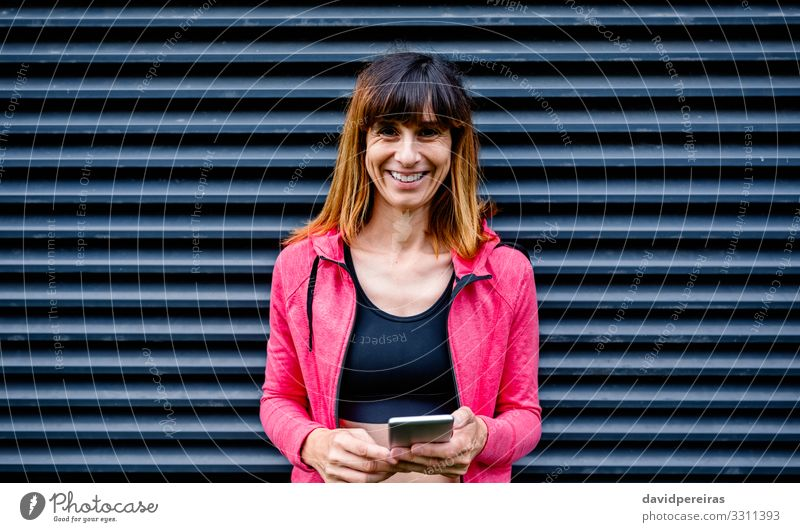 Glückliche Sportlerin mit Mobiltelefon Lifestyle Handy PDA Mensch Frau Erwachsene brünett Fitness Lächeln stehen sportlich dünn Freundlichkeit schwarz