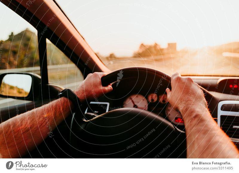 nicht erkennbarer Mann, der das Rad hält und bei Sonnenuntergang fährt. reisekonzept fahren PKW Straße Ferien & Urlaub & Reisen Ausflug Kaukasier unkenntlich