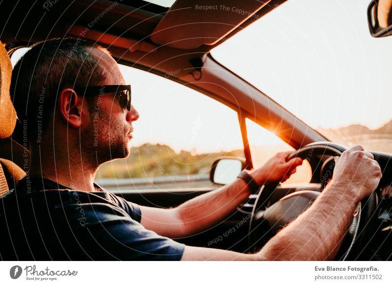 junger Mann am Steuer und am Steuer bei Sonnenuntergang. reisekonzept fahren PKW Straße Ferien & Urlaub & Reisen Ausflug Kaukasier Jugendliche Fahrer reisend