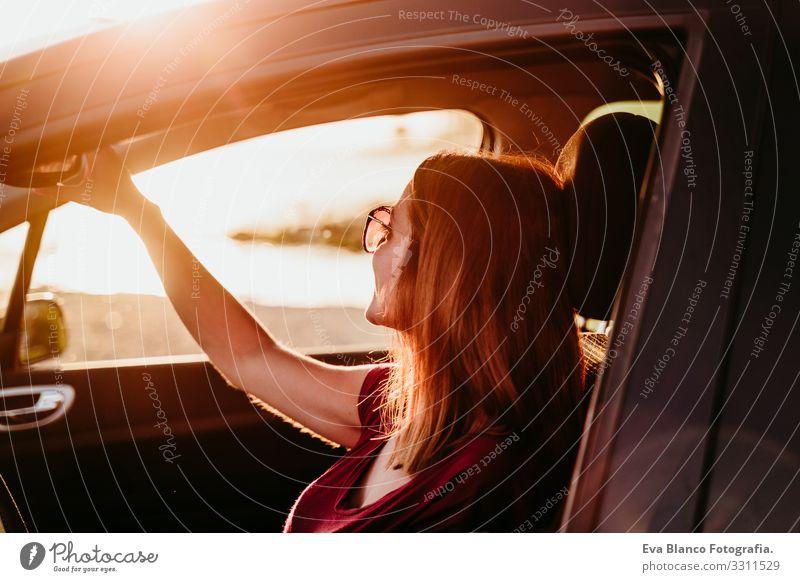 junge Frau, die bei Sonnenuntergang Auto fährt. reisekonzept Jugendliche PKW fahren Strand Fahrer Ferien & Urlaub & Reisen reisend Ausflug Lifestyle Kaukasier