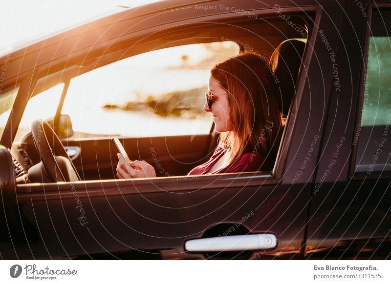 junge Frau, die bei Sonnenuntergang Auto fährt und ein Mobiltelefon benutzt. reisekonzept Jugendliche PKW fahren Strand Fahrer Ferien & Urlaub & Reisen reisend
