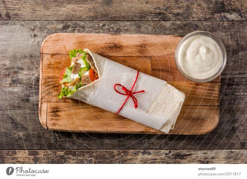 Döner oder Schawarma-Sandwich auf Holztisch. Fleischspieß Kebab Belegtes Brot umhüllen Brötchen Hähnchen Gemüse Tomate Salat Kopfsalat Zwiebel Kräuter & Gewürze