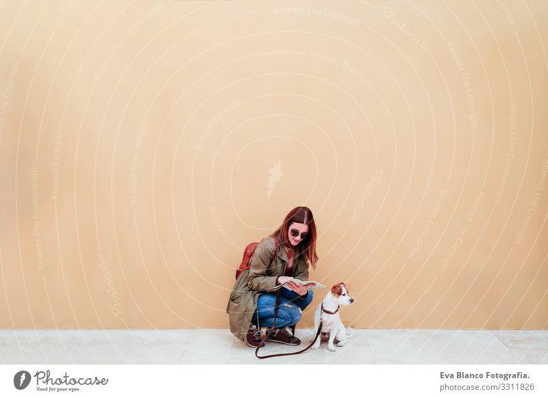 Frau und Hund in der Stadt, gelber Hintergrund. Frau beim Lesen einer Karte. Reise- und Tourismuskonzept reisen Großstadt Landkarte urban Wand jack russell