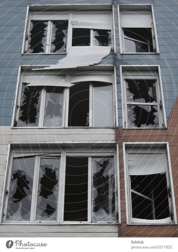 Zerstörte Fassade eines Plattenbaus mit zerbrochenen Fenstern Menschenleer Hochhaus Ruine Bauwerk Gebäude Architektur Wohnplattenbau Mauer Wand bedrohlich Wut