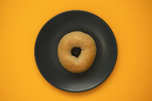 Bagel isoliert auf einer grauen Platte mit orangem Hintergrund. Ansicht von oben. Teigwaren Backwaren Brot Essen Frühstück Diät Herd & Backofen Holz frisch weiß