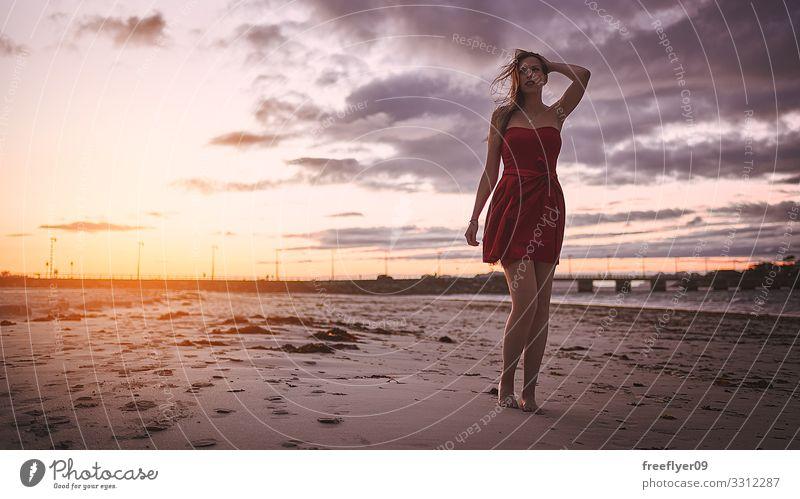 Frau im roten Kleid beim Sonnenuntergang am Strand Reichtum elegant Stil schön Wellness Erholung Duft Ferien & Urlaub & Reisen Sommer Meer Mensch feminin