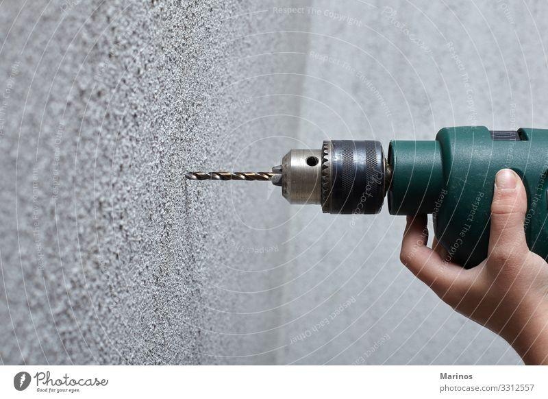 Arbeiter bohrt mit einem Elektrobohrer ein Loch in die Wand. Wohnung Haus Arbeit & Erwerbstätigkeit Werkzeug Mann Erwachsene Hand machen bohren Bohrung Golfloch
