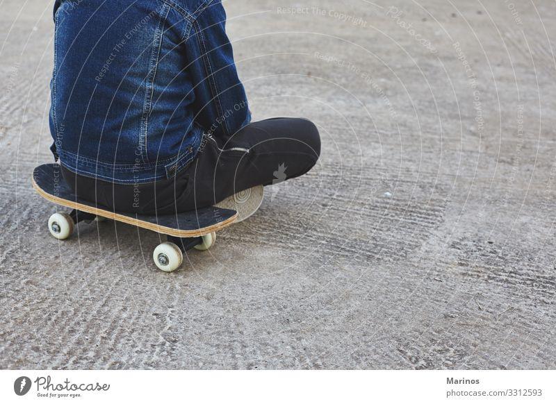 Kinderskateboardfahrer, der auf seinem Skateboard sitzt. Lifestyle Freude Sport Mensch Junge Jugendliche Park Straße Jeanshose Skateboarding Schlittschuh