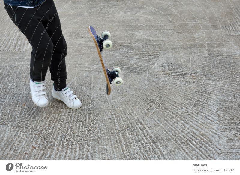 Kleiner Skateboarder, der einen Skateboard-Trick macht. Lifestyle Freude Sport Kind Mensch Junge Jugendliche Park Straße Jeanshose Skateboarding Schlittschuh