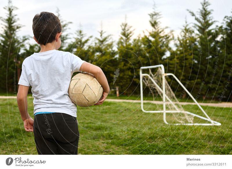 Kind, das einen Fußball auf dem Gartenfeld hält. Lifestyle Freude Glück Spielen Sport Mensch Junge Mann Erwachsene Gras Fröhlichkeit grün Ball Halt jung Kinder