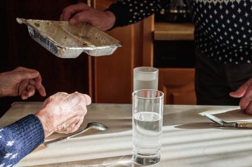 Mittagstisch Frau Mensch Mann alt blau weiß Hand Lebensmittel Essen Senior Zusammensein braun grau Häusliches Leben Wohnung