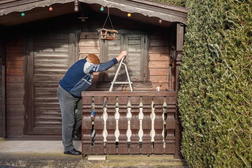 Alter Mann an Leiter Häusliches Leben Wohnung Garten Gartenhaus Futterhäuschen maskulin Männlicher Senior 1 Mensch 60 und älter festhalten machen stehen blau