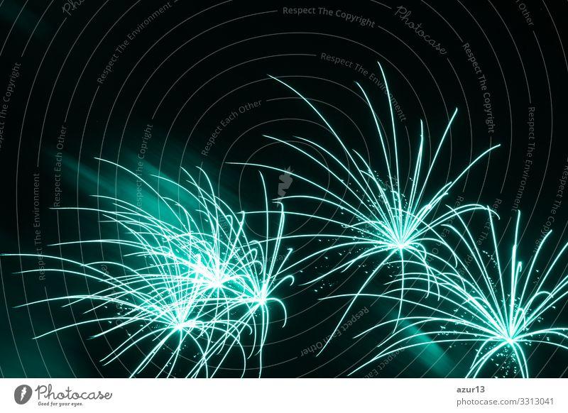 Am Himmel des Luxus-Feuerwerks-Ereignisses sind schöne, feine, türkisfarbene Sterne zu sehen. Unterhaltungs-Sternfeuerwerk mit schwarzem, dunklem Nachthintergrund.
