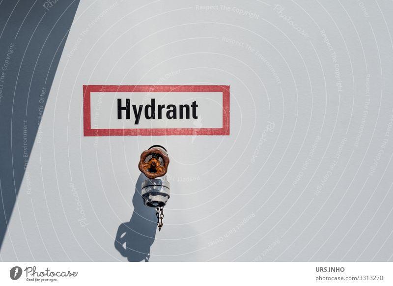 Hydrant vor hellem Hintergrund mit Schild Industrie Metall einfach grau rot weiß Sicherheit Schutz Rettung Anschluss Schriftzeichen Feuerwehr Brandschutz