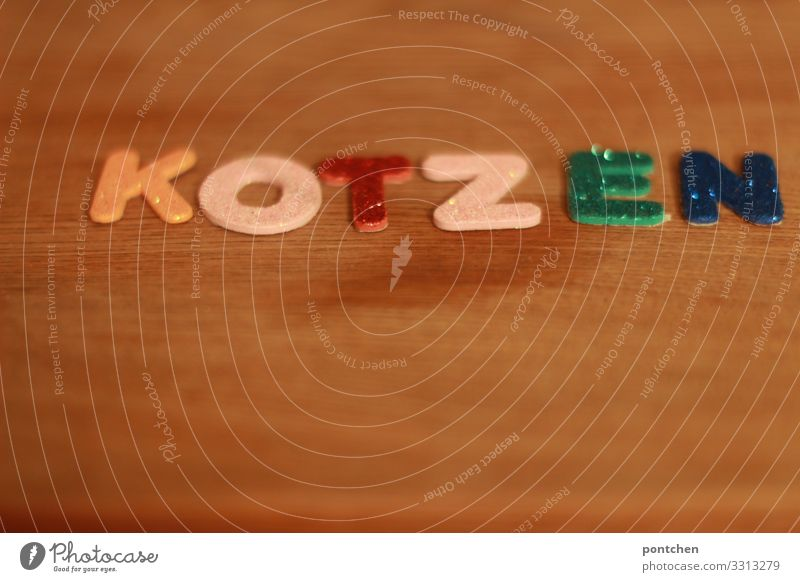 Nahaufnahme. Bunte klebebuchstaben formen das Wort kotzen. Schriftzeichen Kitsch skurril Gesundheit Erbrechen Ärger Symbolismus Aufregung Wut schwanger
