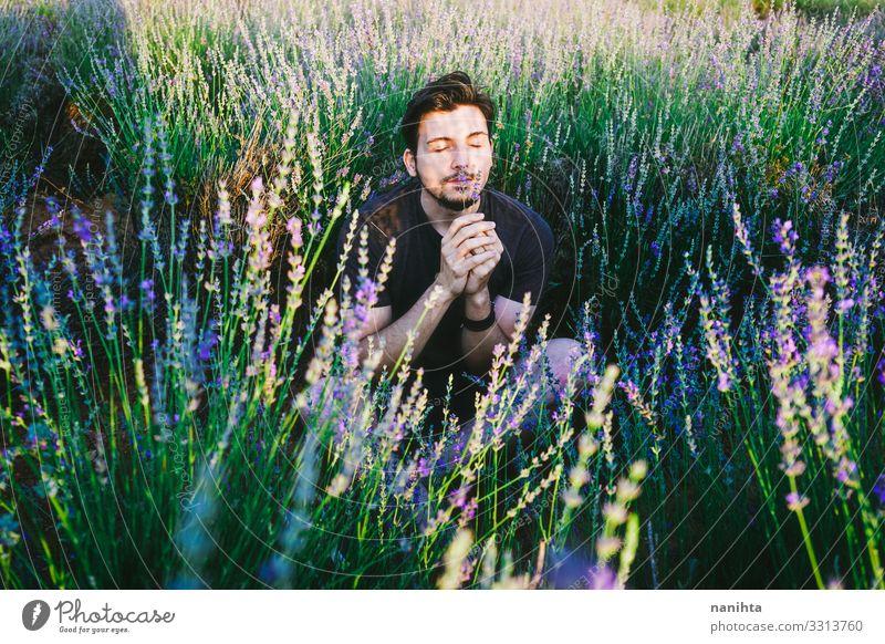 Junger Mann in einem Blumenfeld Maskulinität neu Geschlecht gutaussehend Frühling Schatten Licht Sonne sonnig Lavendel männlich jung Vollbart bärtig lässig