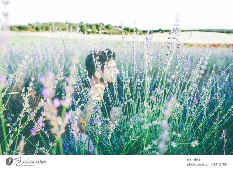 Junger Mann in einem Blumenfeld Gesicht Erholung ruhig Sonne Mensch maskulin Erwachsene 18-30 Jahre Jugendliche 30-45 Jahre Umwelt Natur Frühling Sommer Blüte