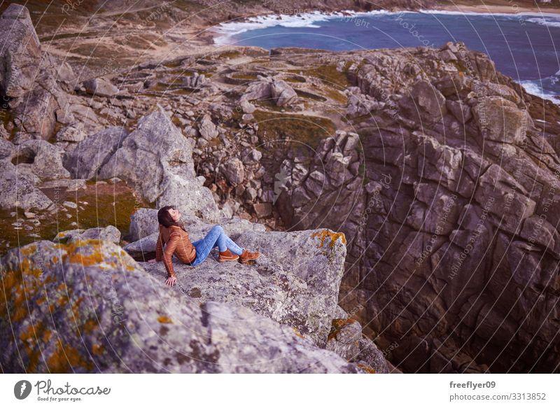 Frau sitzt auf einer Klippe in der Nähe von Baroña Castro in Galizien Barona keltisch Galicia Spanien wandern Tourismus Natur Küstenlinie Steine Landschaft jung