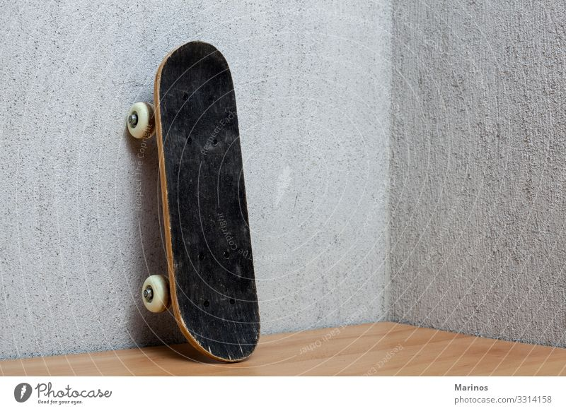 Skateboard, das an einer Wand steht. Lifestyle Sport Junge Straße Schuhe Turnschuh stehen lang grau schwarz Schlittschuh Holzplatte Schlittschuhlaufen