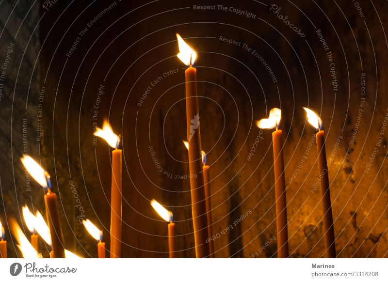 Kerzen in einer orthodoxen Kirche anzünden. Lifestyle Ostern Weihnachten & Advent Feuer leuchten Hoffnung Religion Licht Innenaufnahme