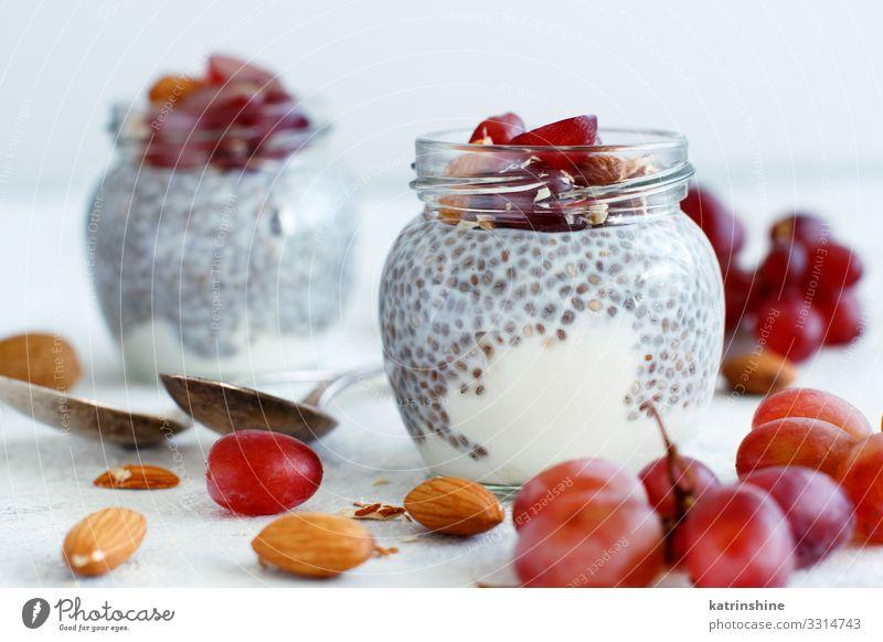 Chia-Puddingparfait mit roten Trauben und Mandeln Joghurt Frucht Dessert Essen Frühstück Diät Löffel dunkel grau weiß Glas Parfait Weintrauben rote Weintrauben