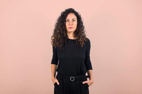 Brünette Frau, die ernst in die Kamera schaut. 30-45 Jahre Einstellung Beautyfotografie braun Freizeitbekleidung in Schwarz gekleidet elegant Ermächtigung