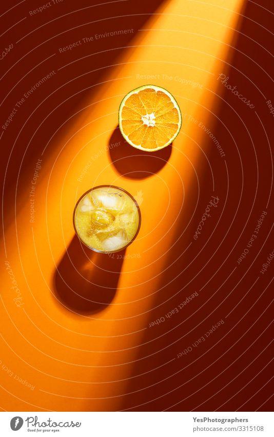 Glas Orangensaft und Orangenscheiben im Sonnenlicht. Frucht Erfrischungsgetränk Limonade Saft obere Ansicht Zitrusfrüchte farbenfroh halbieren trinken