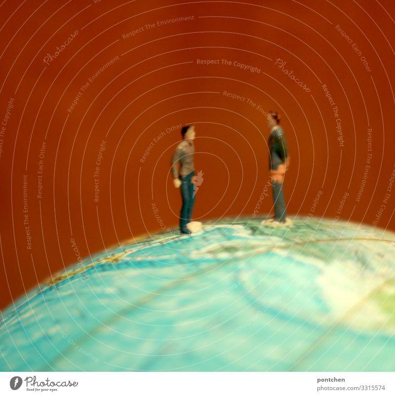 Streit. Zwei Spielfiguren Männer stehen sich auf einem Globus gegenüber. Erdenbürger Mensch maskulin Homosexualität Junger Mann Jugendliche Erwachsene Paar