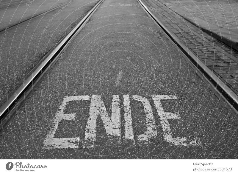 This is the ENDE Stadt weiß schwarz Straße trist Schriftzeichen Buchstaben Ende Gleise Straßenbelag Straßenbahn Verkehrsschild Beschriftung Schienenverkehr