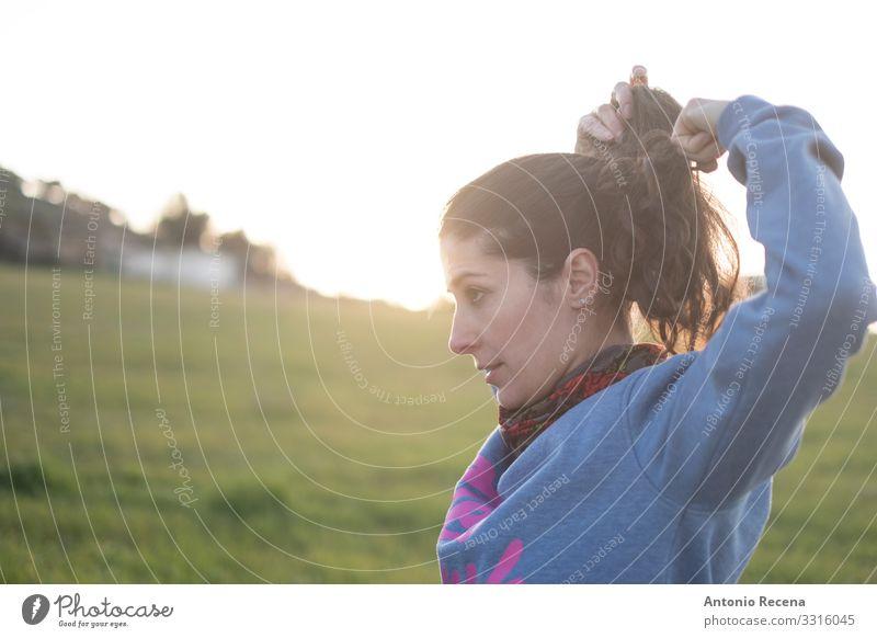 Frau macht vor dem Laufen bei Sonnenuntergang einen Zopf Sport Mensch feminin Erwachsene stehen Pferdeschwanz echte Menschen realistisch offen Spanisch