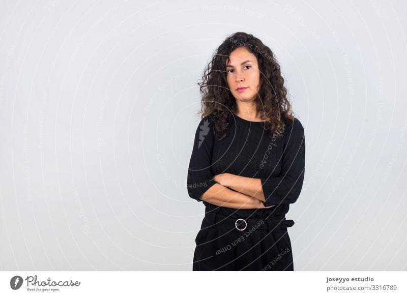 Brünette Frau mit schwarzem Hemd und gekreuzten Armen. 30-45 Jahre Einstellung Beautyfotografie braun Freizeitbekleidung krause Haare in Schwarz gekleidet