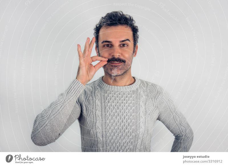 Ein brauner, lächelnder, gutaussehender Mann, der seinen Schnurrbart berührt Erwachsene attraktiv Beautyfotografie Krebs Freizeitbekleidung heiter selbstbewußt