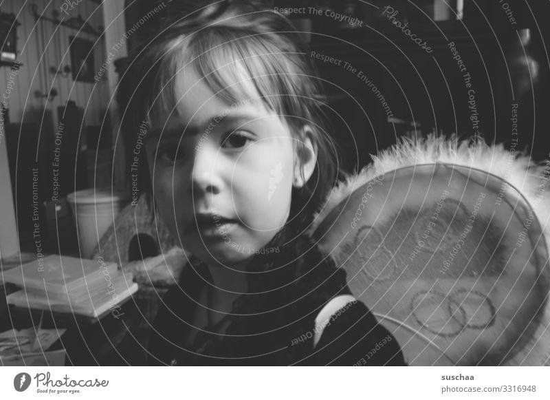 flügelträgerin Kind Kindheit Wohnung Schwarzweißfoto Mädchen Prinzessin Fee Elfenkostüm Flügel Kostüm Karnevalskostüm angemalt Augenbraue Monobraue verkleiden