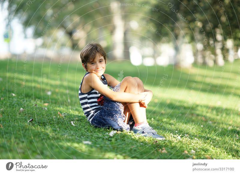 Kleines Mädchen, acht Jahre alt, sitzt auf dem Rasen im Freien. Stil Freude Glück schön Gesicht Spielen Ferien & Urlaub & Reisen Freiheit Sommer Kind Schulkind