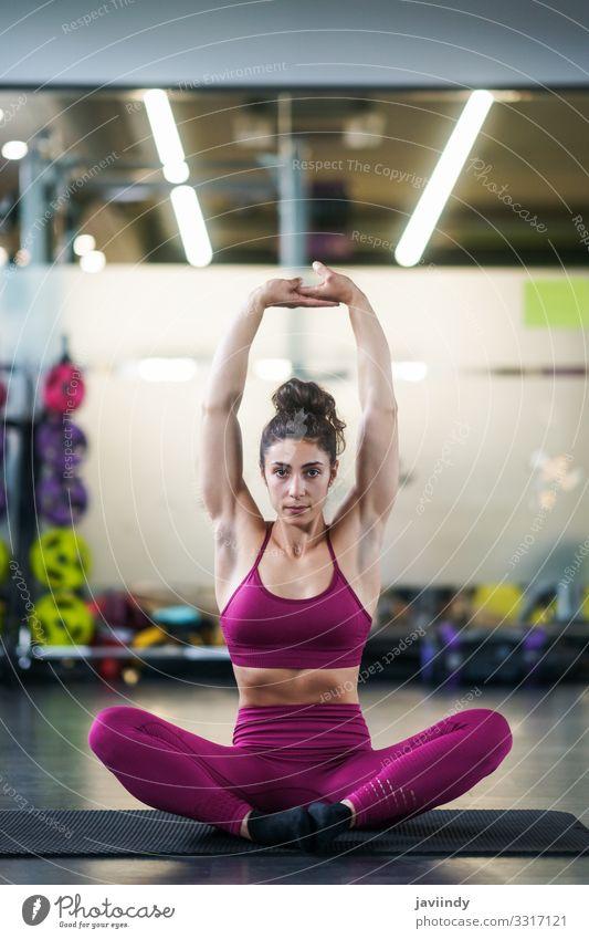 Junge Frau macht Dehnungsübungen auf einer Yogamatte Lifestyle Körperpflege Wellness Club Disco Sport Mensch feminin Jugendliche Erwachsene Arme 1 18-30 Jahre