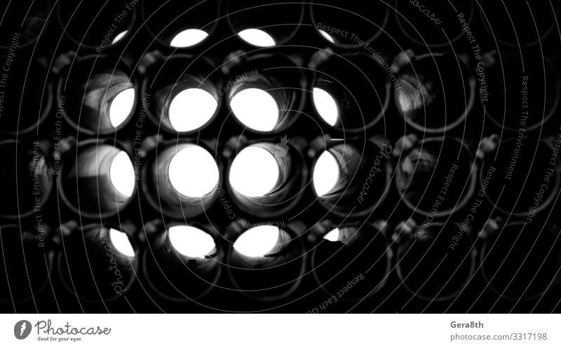 abstrakter dunkler Hintergrund von Rundrohren Metall dunkel trist kreisen Geometrie Golfloch industriell bügeln Licht Monochrom Röhren Wiederholung technisch