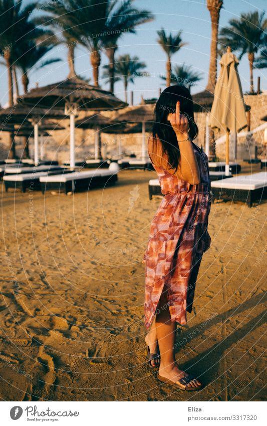 Eine Frau am Strand, die den Mittelfinger in die Kamera hält Junge Frau Jugendliche Erwachsene 18-30 Jahre Wut Streit gereizt Feindseligkeit Aggression Gefühle
