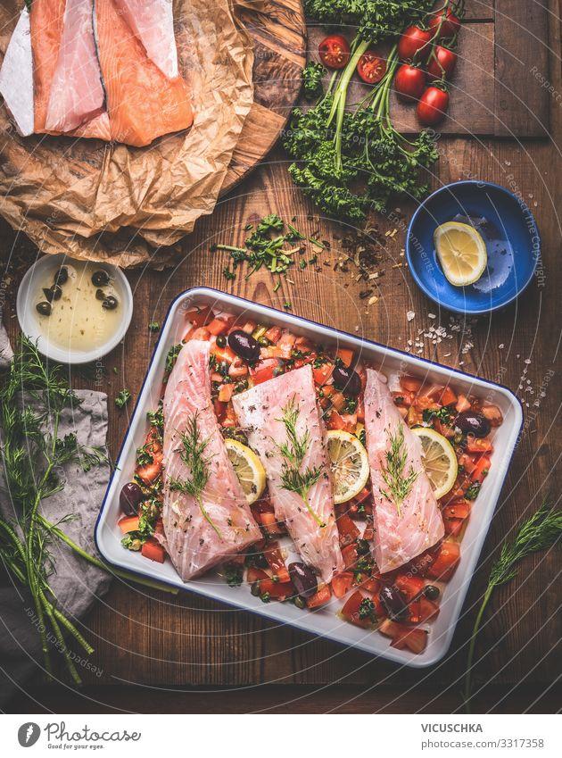 Zubereitung von Bass-Fischfilets in mediterraner Sauce mit Tomaten, Oliven und Kapern in einer Backform auf rustikalem Holzgrund mit Zutaten. Ansicht von oben