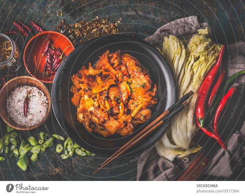 Hausgemachte Kimchi in schwarzer Schale auf rustikalem Hintergrund mit Zutaten: Chinakohl , Chili, Gewürze und Salz . Ansicht von oben. Gesundes fermentiertes Essen