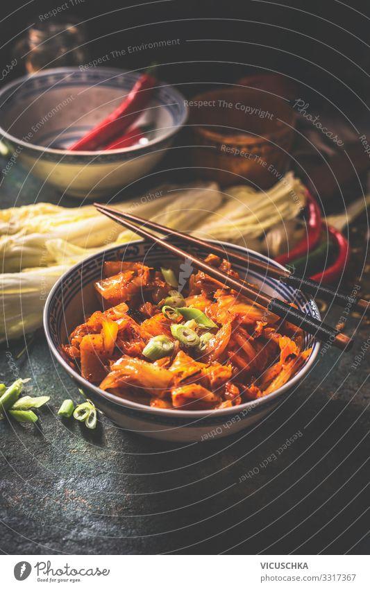 Kimchi, fermentierter Chinakohl in scharfer Chilisauce , in Schale mit Stäbchen auf rustikalem Küchentisch. Nahaufnahme Selleriekohl heiß Peperoni Saucen