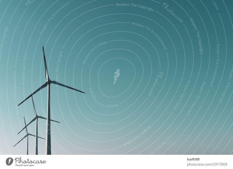 drei gestaffelte Windräder vor winterlich blau türkis farbigem Himmel Technik & Technologie Windkraftanlage Wolkenloser Himmel Sonne Sonnenlicht Schönes Wetter