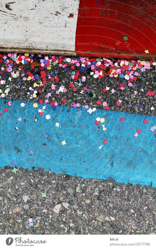 Buntes Konfetti liegt am schmutzigen Donnerstag, während Fasching; Karneval auf der Straße am Boden, zwischen Markierungen als Warnungen, bei einem Karnevalumzug,  und verschmutzt die Umwelt